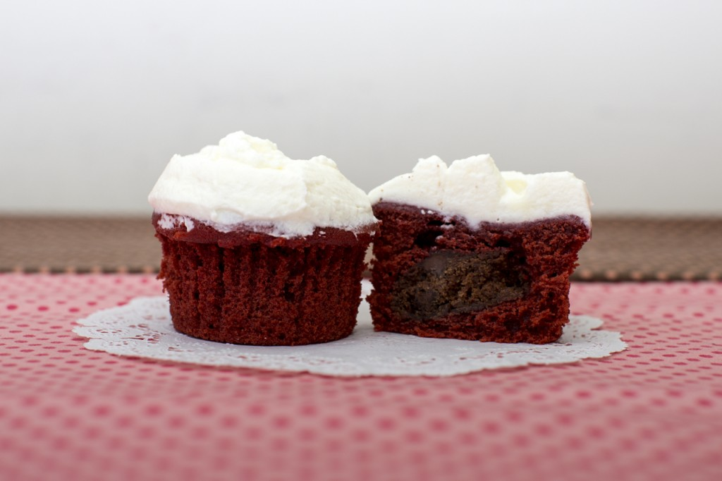 Red Velvet cupcake with chocolate chocolate chip cookie inside topped with mascarpone whipped cream