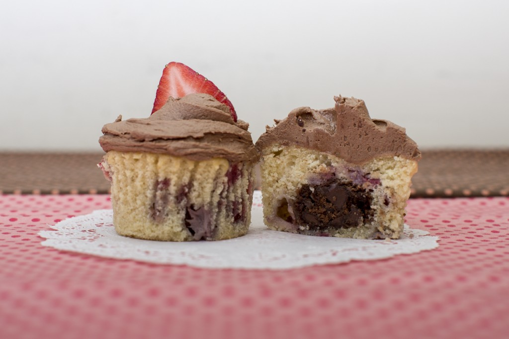 Strawberry cupcake with chocolate chocolate chip cookie inside topped with chocolate buttercream