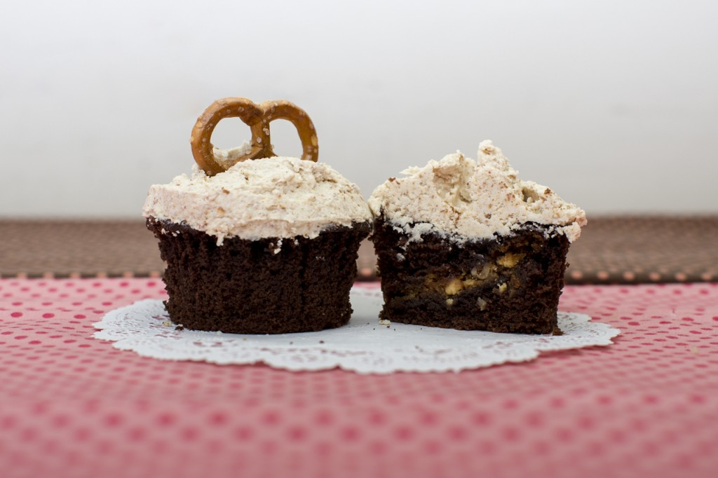 Devil's food cupcake with white chocolate pecan cookie inside topped with pretzel buttercream