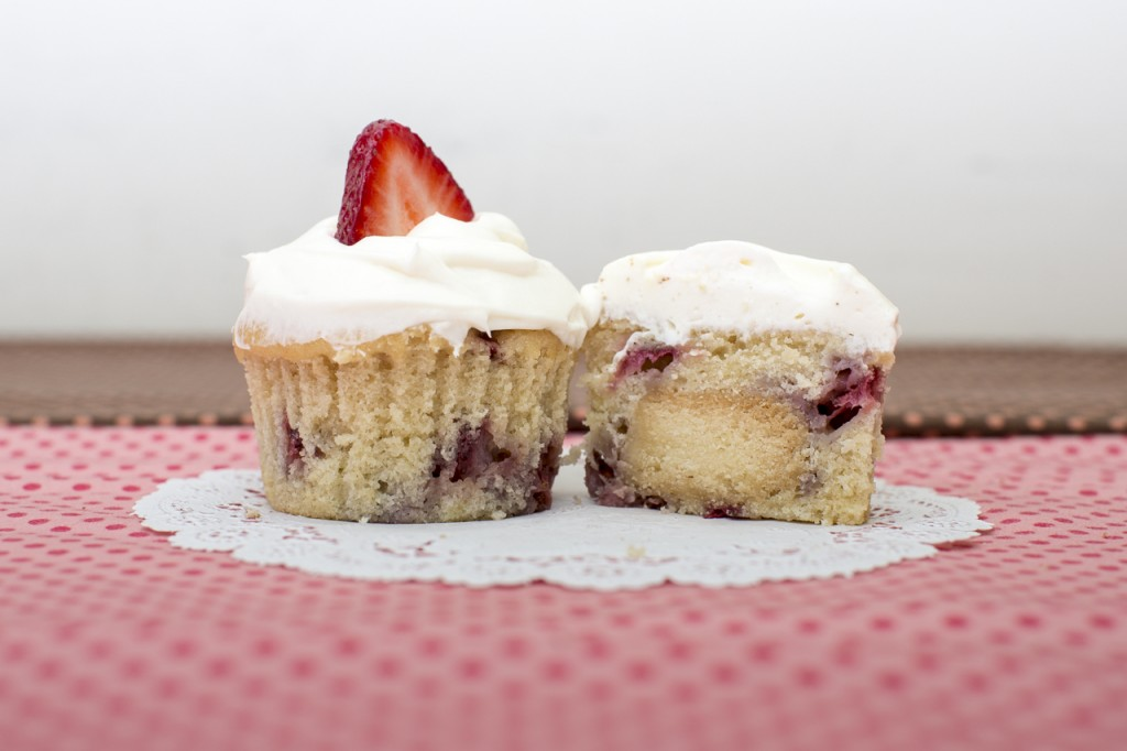 Strawberry cupcake with shortbread inside topped with whipped cream frosting
