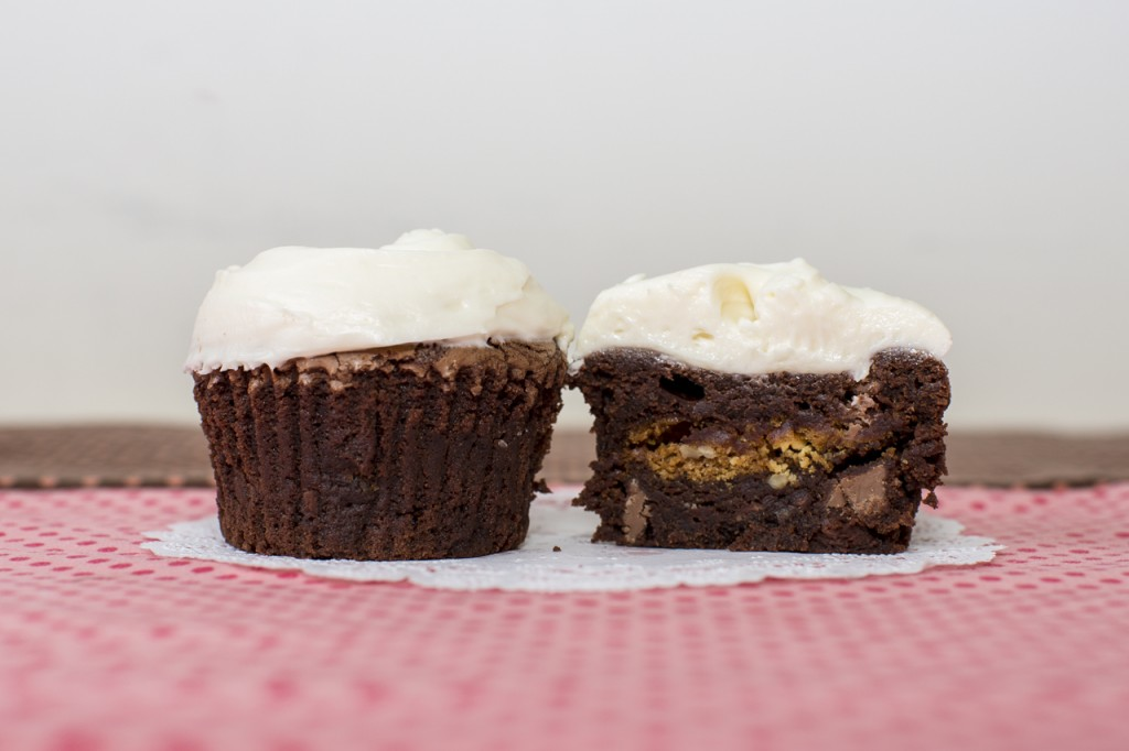 Brownie cupcake with white chocolate pecan cookie inside topped with white chocolate cream cheese frosting