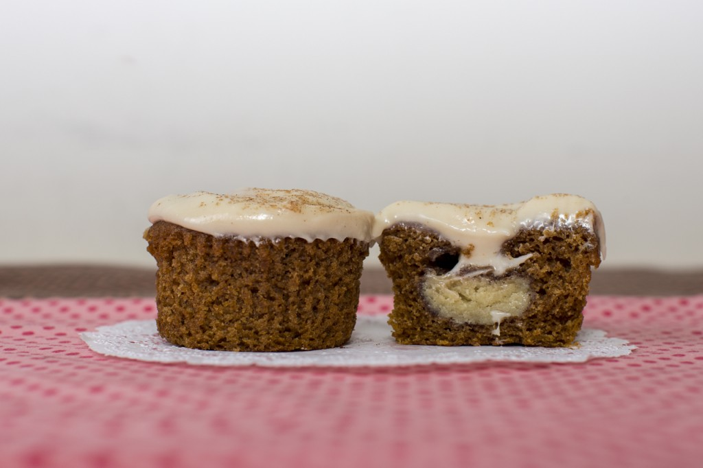 Pumpkin cupcake with snickerdoodle cookie inside topped with maple cream cheese frosting