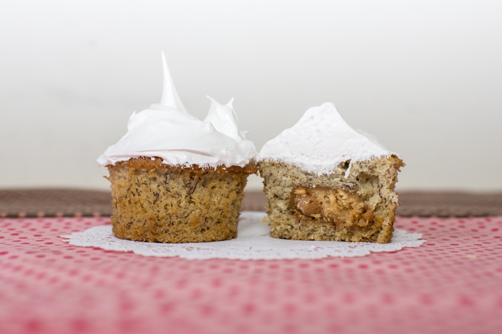 Banana cupcake with peanut butter cookie inside topped with marshmallow frosting